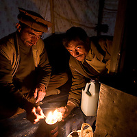 Guide and herder tending to oil-burning candle. Big Pamir, Afghanistan.