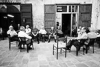 """""""Salento on Street"""".e? un lavoro fotografico che ha come oggetto scene quotidiane, che avvengono in strada o in luoghi pubblici salentini...centro storico di Nardo?-uomini siedono fuori da un circolo"""