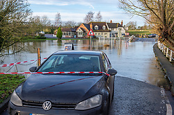 © Licensed to London News Pictures. 22/12/2019. Aylesbury, UK. An car sits on a patch of dry road on Mill Lane in the village of Shabbington after it was pulled from the water, the road was submerged when the River Thame burst its banks during heavy rain across Buckinghamshire. Photo credit: Peter Manning/LNP