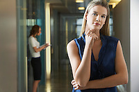 Woman standing in office corridor portrait