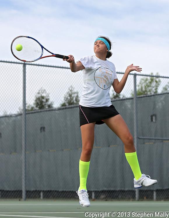 Iowa City West's Megan Jans jumps as she returns the ball during the Class 2A state team tennis tournament at Veterans Memorial Tennis Center in Cedar Rapids on Saturday, June 1, 2013.