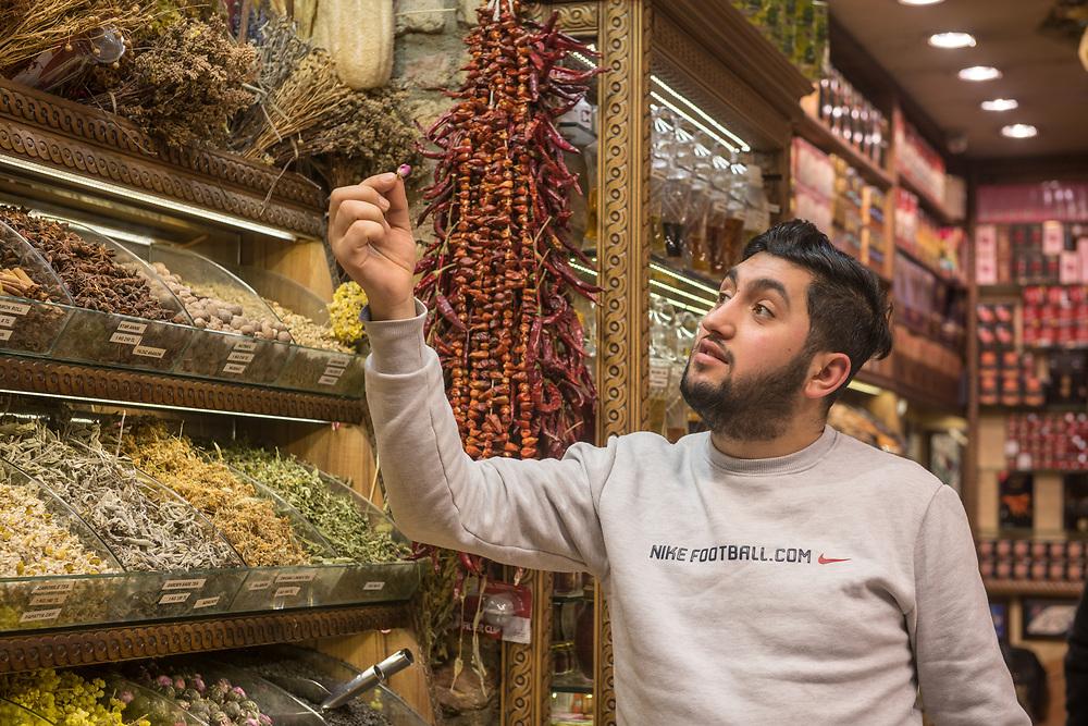 Adult male merchant carefully inspects flower tea in spice shop in Istanbul Spice bazaar in Turkey