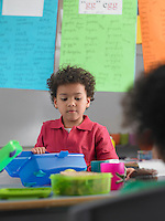 Boy looking into lunch box in classroom