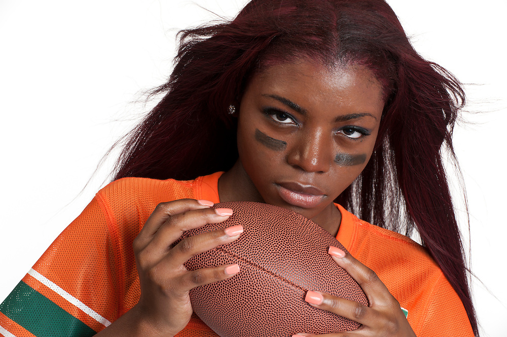 Portrait of young woman holding an american football ball.