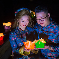 HOI AN , VIETNAM - OCT 04 : Vietnamese couple holding lanterns before droping them into the river in Hoi An ,Vietnam during the Hoi An Full Moon Lantern Festival on October 04 2017