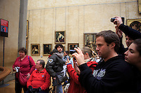A crowd of visitors gathers in front of the Mona Lisa by Leonard DaVinci in The Louvre, Paris, France.