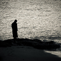 A lone silhouetted man with head bowed, standing at waters edge.