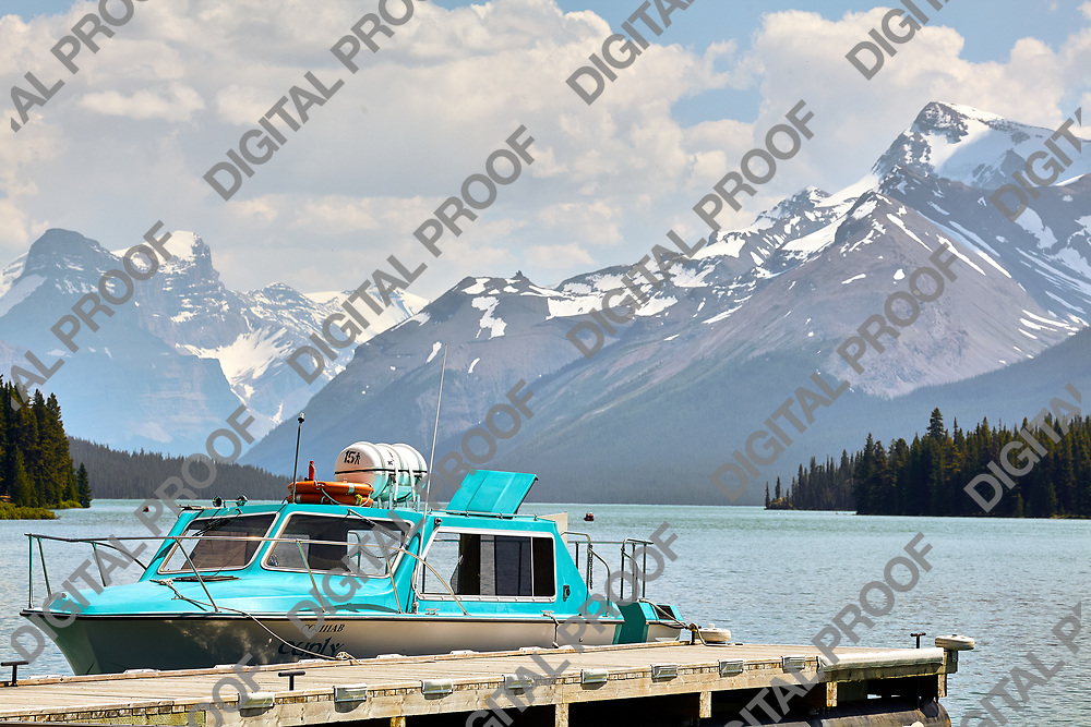 Relaxing Boat in Jasper Lake with Snowy mountains in the background
