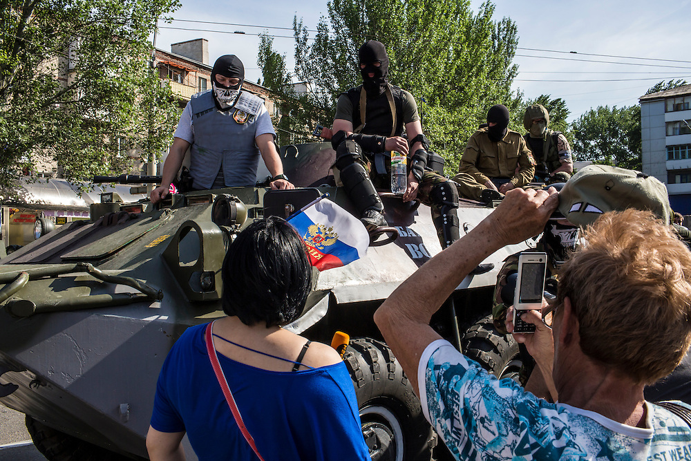 DONETSK, UKRAINE - MAY 20: People photograph members of the Vostok Battalion, a pro-Russia militia, while they stand guard in an intersection on May 20, 2014 in Donetsk, Ukraine. A week before presidential elections are scheduled, questions remain whether the eastern regions of Donetsk and Luhansk are stable enough to administer the vote. (Photo by Brendan Hoffman/Getty Images) *** Local Caption ***