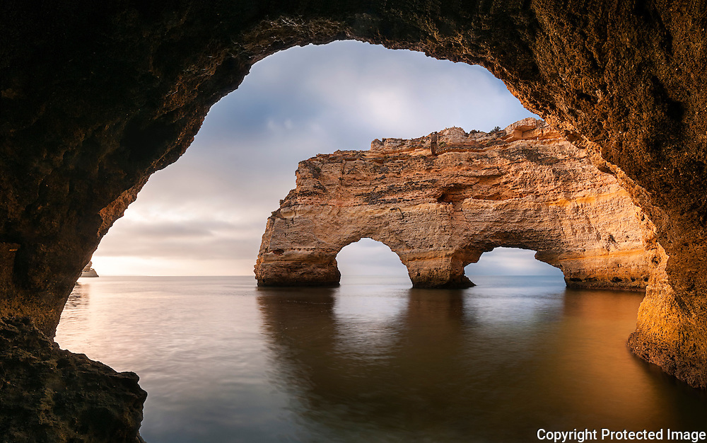 Praia da Marinha famous arcs framed from the inside of a tiny cave at the high tide, in cloudy summer morning.