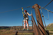 Woman on platform ready to zip line in the Snake River Canyon with Zip the Snake in Twin Falls, Idaho.