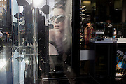 A man browses shelves of sunglasses plus a healthy poster girl for Burberry sunglasses they call Eyewear, in a sunlit London street. With other Londoners and shoppers passing-by outside, the young male shops inside the store. Burberry Group plc is a British luxury fashion house, manufacturing clothing, fragrance, and fashion accessories.