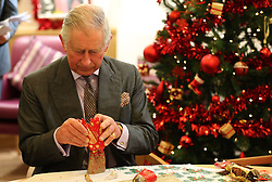 The Prince of Wales looks inside a Christmas cracker during a visit to the Sue Ryder Leckhampton Court Hospice near to Cheltenham in Gloucestershire, which he visits regularly and is celebrating 30 years of royal patronage.