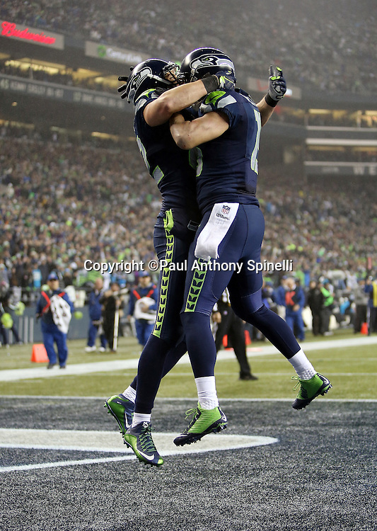 Seattle Seahawks tight end Luke Willson (82) leaps and celebrates with Seattle Seahawks wide receiver Jermaine Kearse (15) in the end zone after catching a 25 yard fourth quarter touchdown pass for a 24-10 Seahawks lead during the NFL week 19 NFC Divisional Playoff football game against the Carolina Panthers on Saturday, Jan. 10, 2015 in Seattle. The Seahawks won the game 31-17. ©Paul Anthony Spinelli