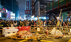 Hong Kong, China. 13th October 2019. Woman suspected of being pro-Beijing is assaulted by pro-democracy protestors in Mongkok district in Kowloon on Sunday evening. This incident was one of several throughout Hong Kong on Sunday which saw acts of vandalism carried out by a minority in the pro-democracy movement. Crowd stands behind barricade on Nathan Road. Iain Masterton/Alamy Live News.