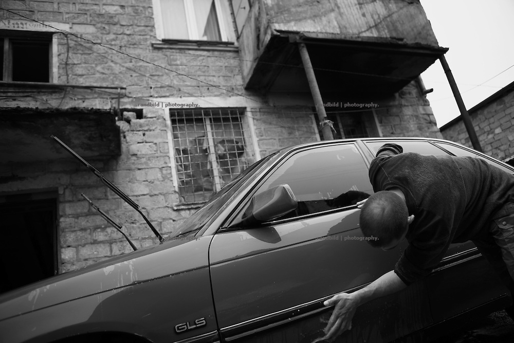 "A man celan his car. This image is part of the photoproject ""The Twentieth Spring"", a portrait of caucasian town Shushi 20 years after its so called ""Liberation"" by armenian fighters. In its more than two centuries old history Shushi was ruled by different powers like armeniens, persians, russian or aseris. In 1991 a fierce battle for Karabakhs independence from Azerbaijan began. During the breakdown of Sowjet Union armenians didn´t want to stay within the Republic of Azerbaijan anymore. 1992 armenians manage to takeover ""ancient armenian Shushi"" and pushed out remained aseris forces which had operate a rocket base there. Since then Shushi became an ""armenian town"" again. Today, 20 yeras after statement of Karabakhs independence Shushi tries to find it´s opportunities for it´s future. The less populated town is still affected by devastation and ruins by it´s violent history. Life is mostly a daily struggle for the inhabitants to get expenses covered, caused by a lack of jobs and almost no perspective for a sustainable economic development. Shushi depends on donations by diaspora armenians. On the other hand those donations have made it possible to rebuild a cultural centre, recover new asphalt roads and other infrastructure. 20 years after Shushis fall into armenian hands Babies get born and people won´t never be under aseris rule again. The bloody early 1990´s civil war has moved into the trenches of the frontline 20 kilometer away from Shushi where it stuck since 1994. The karabakh conflict is still not solved and could turn to an open war every day. Nonetheless life goes on on the south caucasian rocky tip above mountainious region of Karabakh where Shushi enthrones ever since centuries."