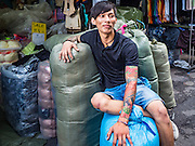 12 JANUARY 2017 - BANGKOK, THAILAND:        A worker in Bo Bae Market sits in front of his shop and waits for customers. Bo Bae Market is a sprawling wholesale clothing market in Bangkok. There are reportedly more than 1,200 stalls selling clothes made in Thailand and neighboring countries. Bangkok officials have threatened to shut down parts of Bo Bae market, but so far it has escaped the fate of the other street markets that have been shut down.     PHOTO BY JACK KURTZ