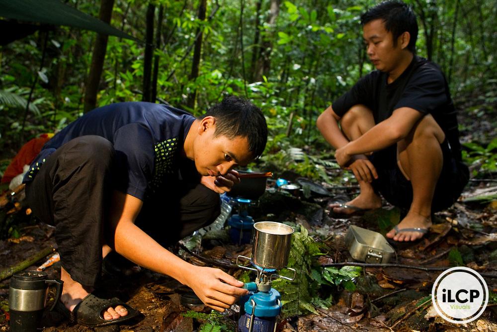 Bornean Clouded Leopard (Neofelis diardi borneensis) researchers Rizam Bakiri and Hildey Baas making food at campsite, Tawau Hills Park, Sabah, Borneo, Malaysia