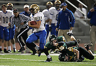 Wahlert's Sam Koenig (17) tries to escape from Kennedy's Andrew Johnson (25)  during the first half of the game between Cedar Rapids Kennedy and Dubuque Wahlert at Kingston Stadium in Cedar Rapids on Friday night, October 21, 2011.