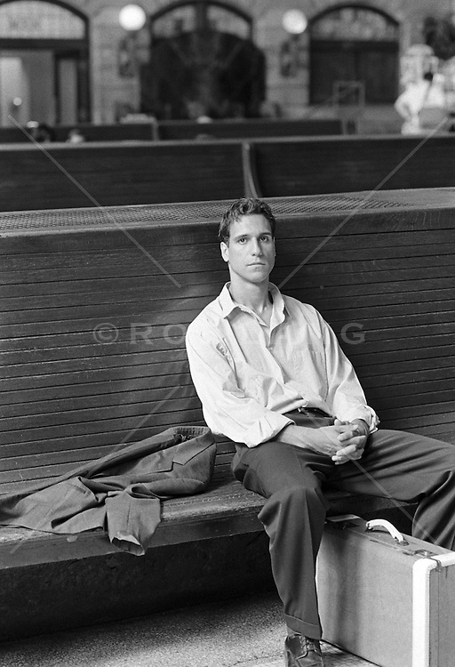 man sitting in the waiting area of a train station in New Jersey