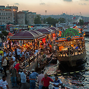 "In the evening in Istanbul, brightly lit fish boats beckon with a promise of a savory treat. For about a century, fishermen have been bringing their catch from the Bosphorus and the Sea of Marmara to Istanbul's Galata Bridge over the Golden Horn for sale. Shouting: ""Balık ekmek! Balık ekmek!"" (Fish in bread! Fish in bread!) a lively scene unfolds bt the water."