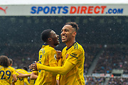 Pierre-Emerick Aubameyang (#14) of Arsenal FC is all smiles as he celebrates with Ainsley Maitland-Niles (#15) of Arsenal FC after scoring a goal during the Premier League match between Newcastle United and Arsenal at St. James's Park, Newcastle, England on 11 August 2019.