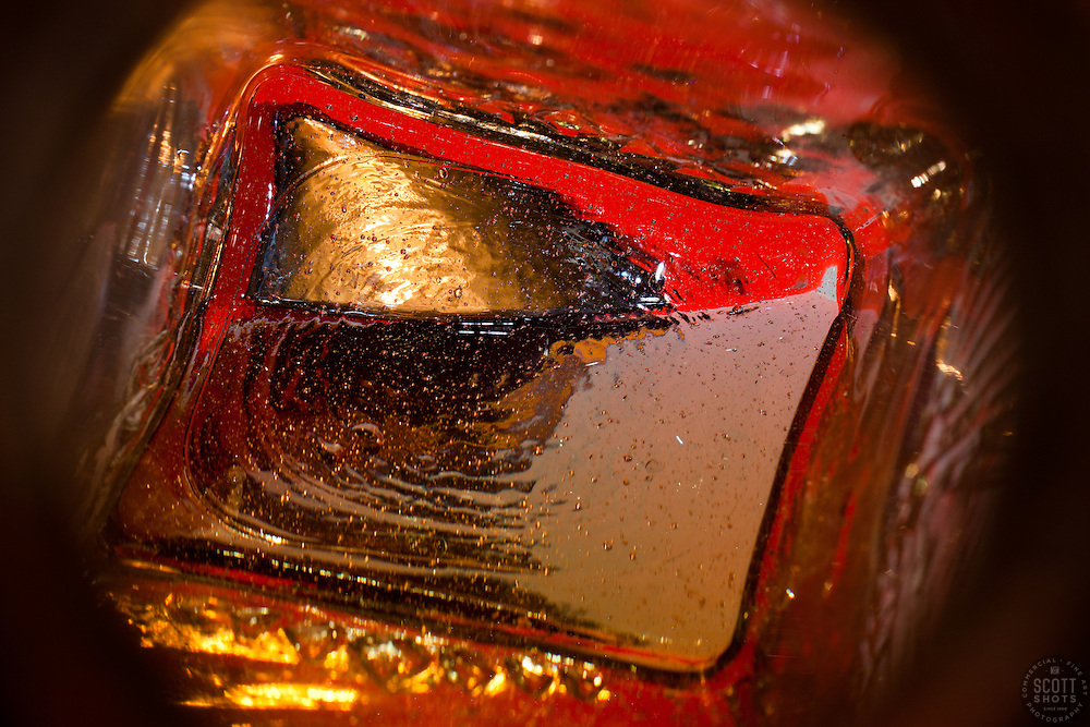 """""""Beauty at the Bottom: Tequila Sunrise 1"""" - This image is a photograph of a tequila bottle looking right down the mouth of the bottle."""