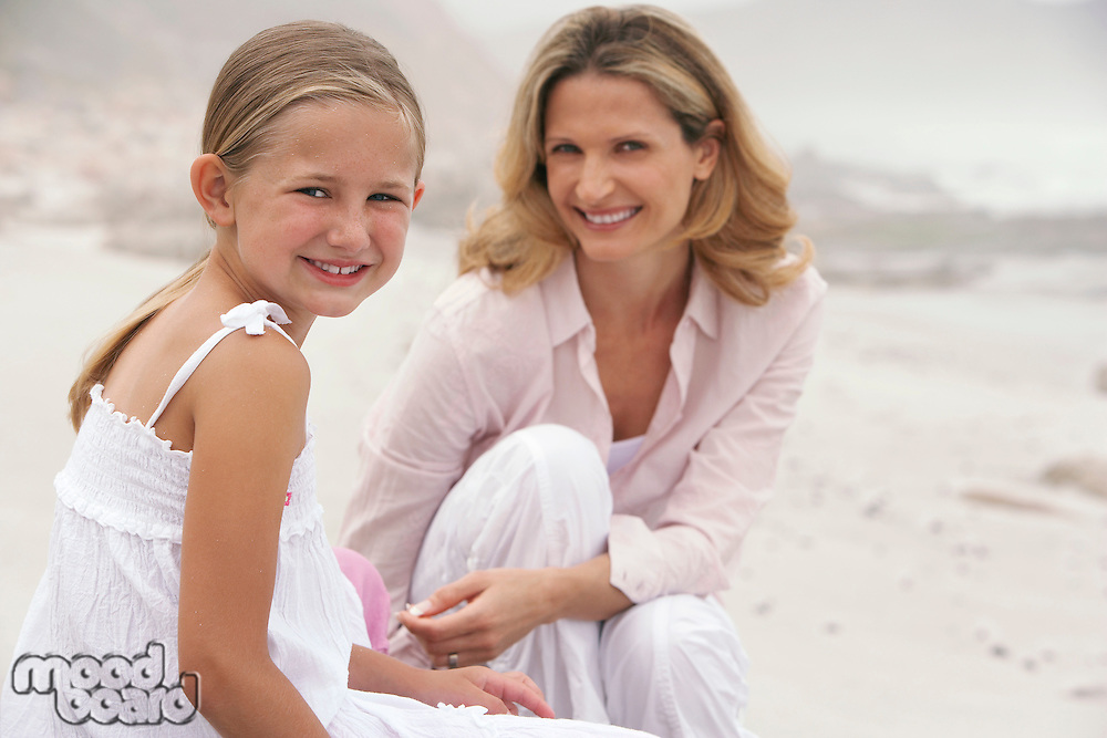 Mother and daughter (7-9) sitting on beach portrait