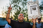 "23 JUNE 2012 - PHOENIX, AZ:    A human rights activist leads chants against the Maricopa County Jail in Phoenix Saturday afternoon. About 2,000 members of the Unitarian Universalist Church, in Phoenix for their national convention, picketed the entrances to the Maricopa County Jail and ""Tent City"" Saturday night. They were opposed to the treatment of prisoners in the jail, many of whom are not convicted and are awaiting trial, and Maricopa County Sheriff Joe Arpaio's stand on illegal immigration. The protesters carried candles and sang hymns.   PHOTO BY JACK KURTZ"