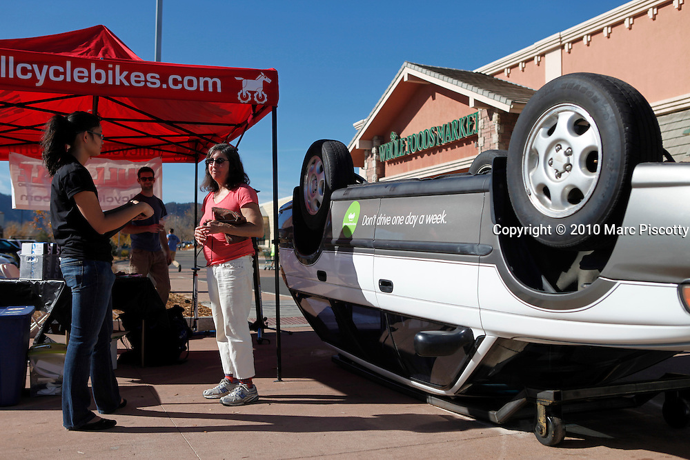 SHOT 11/6/10 12:55:03 PM - Members of Driven to Drive Less display a car turned upside down and offer free bike tunes and maintenance in front of the Whole Foods grocery store in Boulder, Co. on Saturday November 7, 2010. Driven to Drive Less is a program being undertaken by the city of Boulder, Co. that encourages participants to stimulate long term travel behavior change and to creatively demonstrate to the general public the ability of Boulder residents to live car free or car lite. Participants receive benefits and discounts at local stores for pledging to give up driving their vehicle one day a week. (Photo by Marc Piscotty / © 2010)