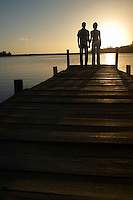 Couple standing on dock by lake holding hands back view.