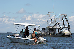 21 August 2010. Barataria Bay, south Louisiana. <br /> Fishing grounds reopen. A shrimp boat sits in the current deploying nets instead of oil boom in the water as recreational fishermen return to fish for speckled trout enjoying a day out in the bay.<br /> Photo credit; Charlie Varley/varleypix.com