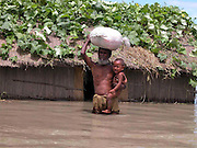 Flood victim an unidentified village old man leaves his house with his grandson through floodwaters after their house is submerged by floodwaters at sialmari, about 329 kilometers southwest of Gauhati, the capital city of Northeastern Indian state, Assam, Monday, June 28, 2004. ..Floodwaters of the Asia'a one of the largest river, Brahmaputra and its 35 tributaries have affected more than one million in all of Indian subcontinent and disrupted communication in many parts of the India and Bangladesh, sources said.  (AP Photo/ Shib Shankar Chatterjee).