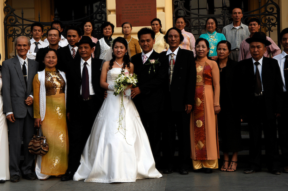 Vietnam: Hanoi..Newlyweds have the family photographs taken on the steps of the Opera House.