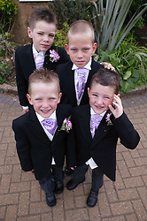 Group of pageboys standing together outside church,