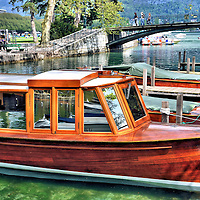 Moored Wooden Boats on Vassé Canal in Annecy, France<br /> These handsome, old wooden cabin cruisers are moored at a dock in the Vassé Canal along Quai Jules Philippe. In the background are the Bridge of Lovers, the Promenade Jacquet and Lac d'Annecy.