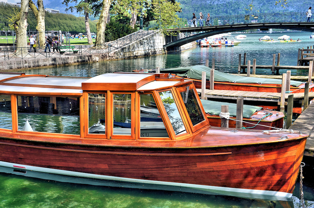 Moored Wooden Boats on Vass&eacute; Canal in Annecy, France<br /> These handsome, old wooden cabin cruisers are moored at a dock in the Vass&eacute; Canal along Quai Jules Philippe. In the background are the Bridge of Lovers, the Promenade Jacquet and Lac d&rsquo;Annecy.