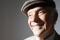 Senior man in flat cap close up in studio