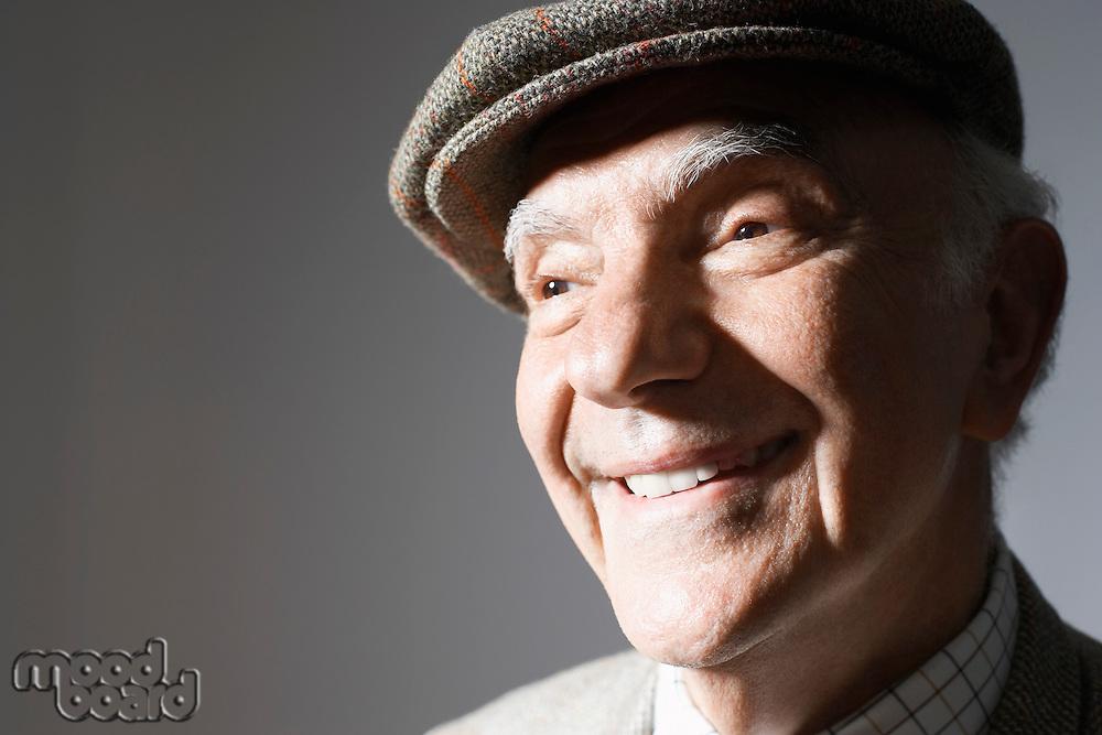 Senior man in flat cap close up in studio