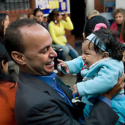 Congressman Luis Gutierrez (D,IL) plays with a baby during CARE's Learning Tour visit to the San Cosme Health Center. San Cosme is a slum in Lima that has the highest rate of tuberculosis in Lima, but has limited health services for the community. The Global Fund is supporting services in San Cosme's health center.