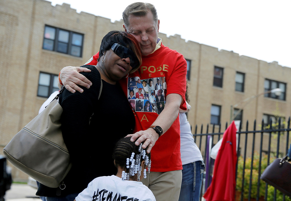 "Father Michael Pfleger (R) comforts Lutrice Boyd and her granddaughter Faith Davis during a news conference by ""Purpose over Pain"", a group of mothers who lost children to gun violence, calling for a stop to shootings in Chicago, Illinois, United States, in this May 6, 2016 file photo.  REUTERS/Jim Young"
