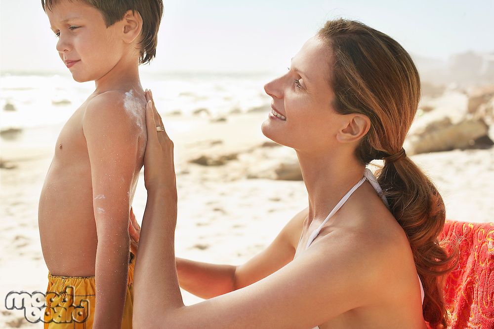 Mother applying protective cream on son's (5-6) back on beach