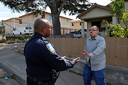 Salinas police officers Jeffrey Lofton listens to a resident of Fremont Street, in the CASP coverage area. The Community Alliance for Safety and Peace is an ambitious program that aims to steer youth away from gang violence and toward solutions offered by more than 30 local organizations offering alternatives.
