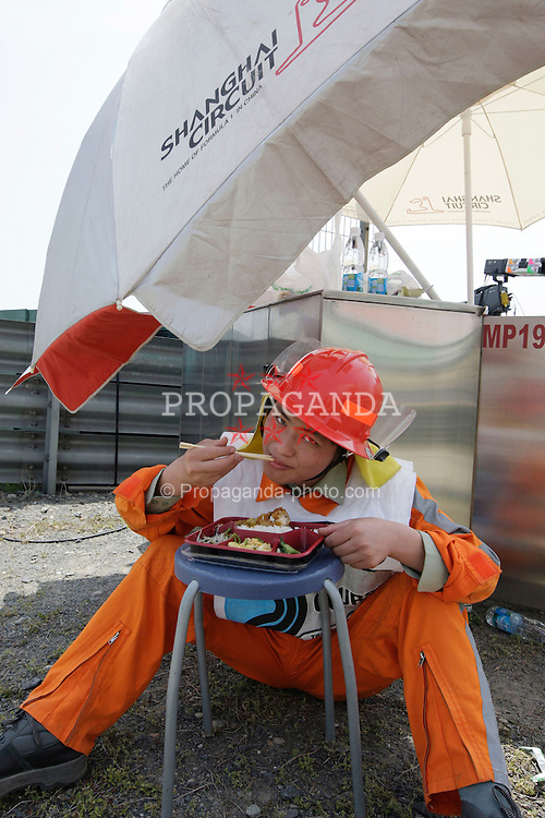 SHANGHAI, CHINA - Saturday, April 18, 2009: A Chinese track marshal takes a meal break on the side of the track during qualifying for the Formula One Grand Prix of China at the Shanghai International Circuit. (Pic by Michael Kunkel/Hoch Zwei/Propaganda)