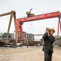 China, Chongqing, Workman carries heavy box at sprawling Chongqing Dongfeng Shipyard on autumn morning
