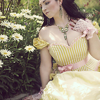 A brunette woman in her 20s wearing a beautiful yellow springtime dress with flowers in her hair, gazing at fresh daisies outdoors