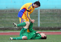 Razvan Ochirosii of Romania helps injured Armin Bacinovic (8)  of Slovenia during Friendly match between U-21 National teams of Slovenia and Romania, on February 11, 2009, in Nova Gorica, Slovenia. (Photo by Vid Ponikvar / Sportida)
