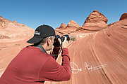 A man takes a picture of pyramid shaped sandstone formations in Coyote Buttes North.