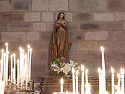 Statue and candles in Notre Dame du Bout du Pont church. Many pilgrims and walkers stopped in here to pray for a safe journey across the Pyrenees Mountains and on to Santiago de Compostela.