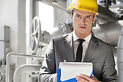 Portrait of confident young male supervisor writing on clipboard in industry